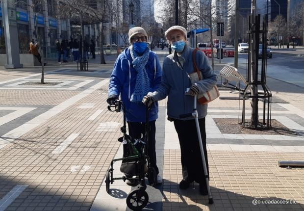 dos personas mayores con bastones y mascarillas